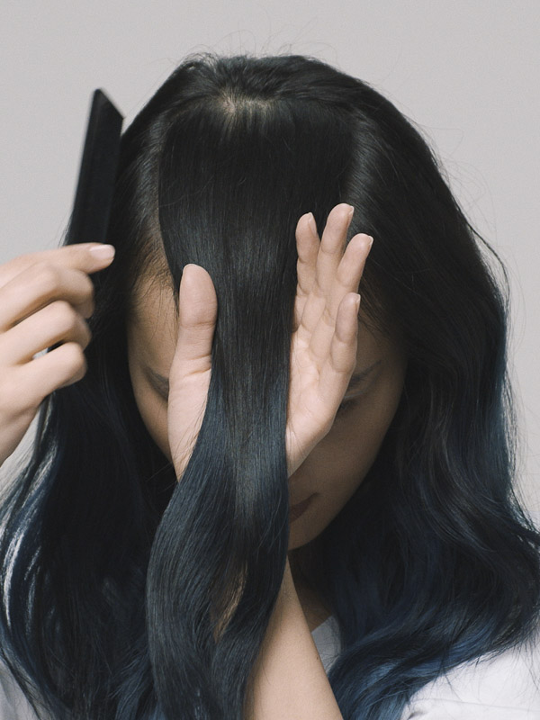 Woman sectioning hair with a comb.